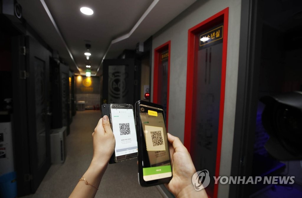Local government officials check whether QR code-based logs are working at a karaoke establishment in Gwangju's Buk Ward, southwestern South Korea, on June 9, 2020, in this photo provided by the ward office. (PHOTO NOT FOR SALE) (Yonhap)