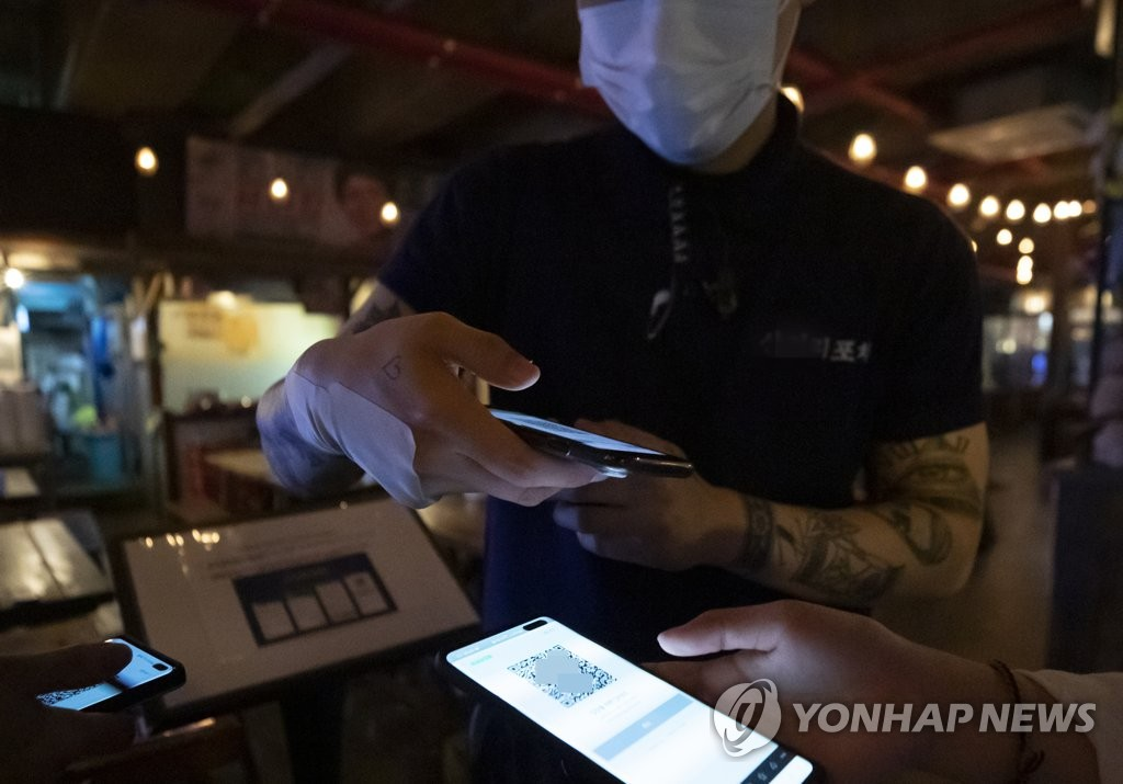 In the photo, taken June 10, 2020, a customer uses a QR code-based registration system to sign an entry log at a bar in Seoul. (Yonhap)