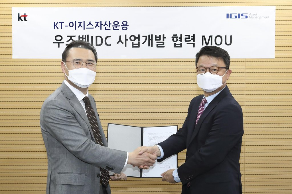 This photo provided by KT Corp. on June 17, 2020, shows Kim Youngwoo (R), head of KT's global business office, and Kang Young-goo, co-CEO of Igis Asset Management Ltd., posing for a photo after signing a partnership on internet data center business opportunities in Uzbekistan. (PHOTO NOT FOR SALE) (Yonhap)