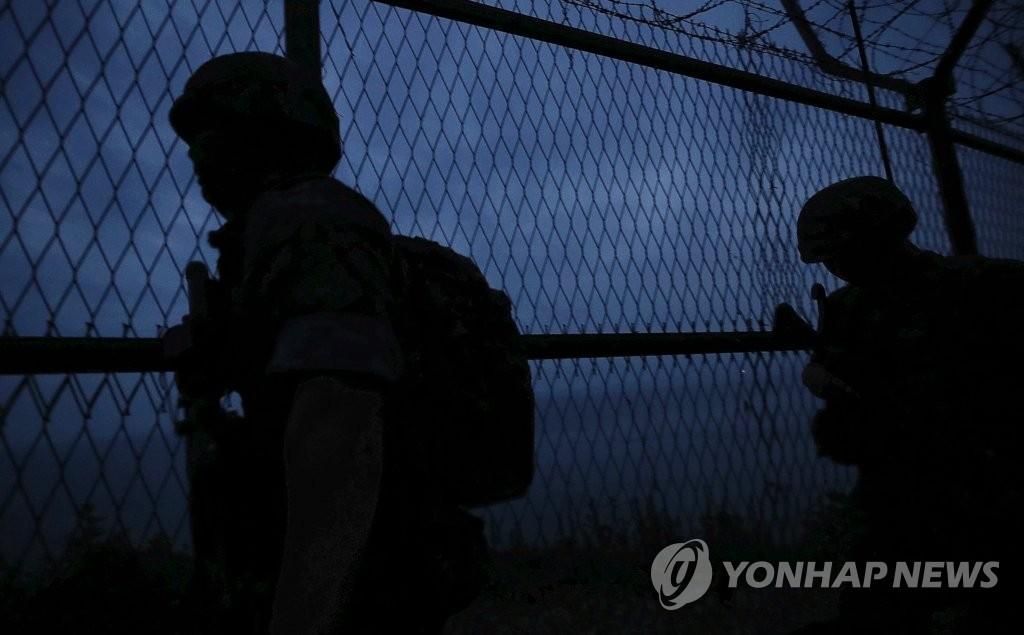 In this file photo, taken on June 23, 2020, South Korean marines patrol along a barbed wire fence on the western border island of Yeonpyeong. (Yonhap)