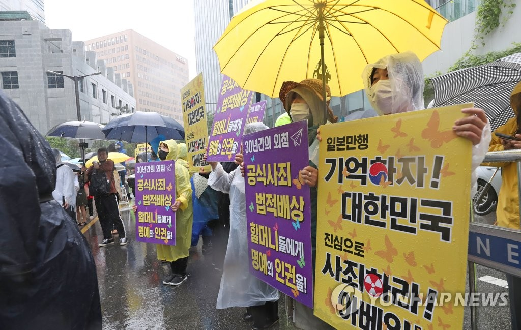 This photo taken on June 24, 2020, shows participants in a weekly rally supporting comfort women holding pickets at the former site of the Japanese Embassy in Seoul's Jongno Ward. (Yonhap)