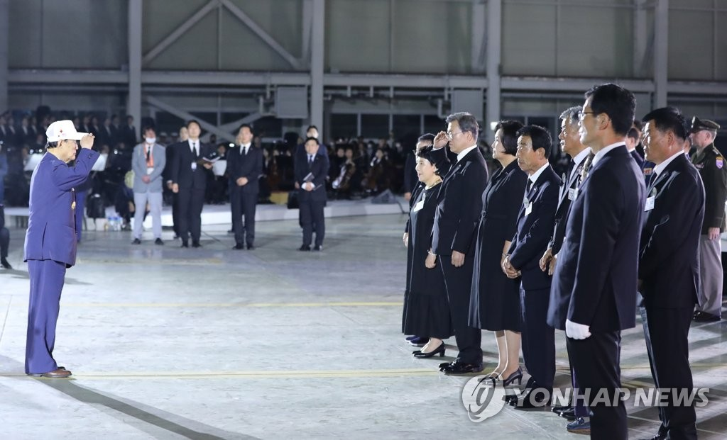 A Korean War veteran (L) salutes President Moon Jae-in during a ceremony at the hangar of Seoul Air Base in Seongnam, southeast of Seoul, on June 25, 2020 to mark the 70th anniversary of the conflict's outbreak. (Yonhap)