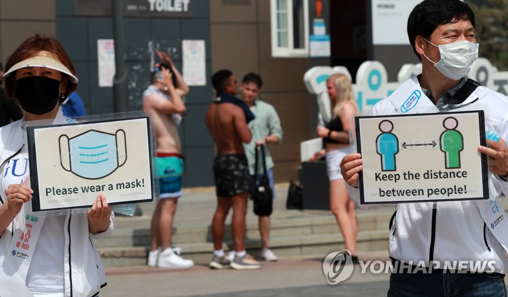 Officials from the Busan city government hold signs to emphasize virus prevention measures at Haeundae Beach in Busan on July 5, 2020. (Yonhap)