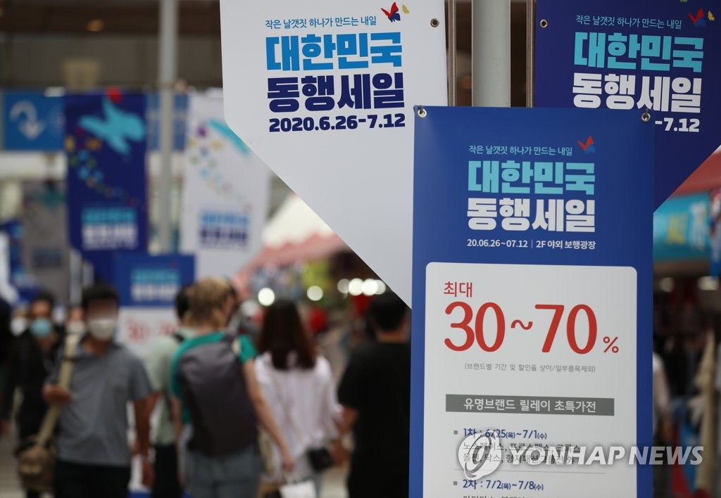 Shoppers browse in an outlet store in Seoul on July 12, 2020, the last day of a state-led sales festival aimed at boosting spending amid the coronavirus outbreak. (Yonhap)
