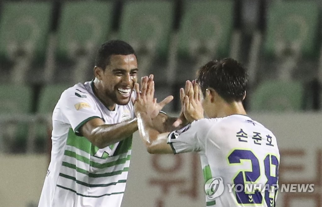 Gustavo of Jeonbuk Hyundai Motors (L) high-fives his teammate Son Jun-ho after completing a hat trick against Busan IPark during the teams' quarterfinals match at the Korea Football Association Cup at Busan Gudeok Stadium in Busan, 450 kilometers southeast of Seoul, on July 29, 2020. (Yonhap)