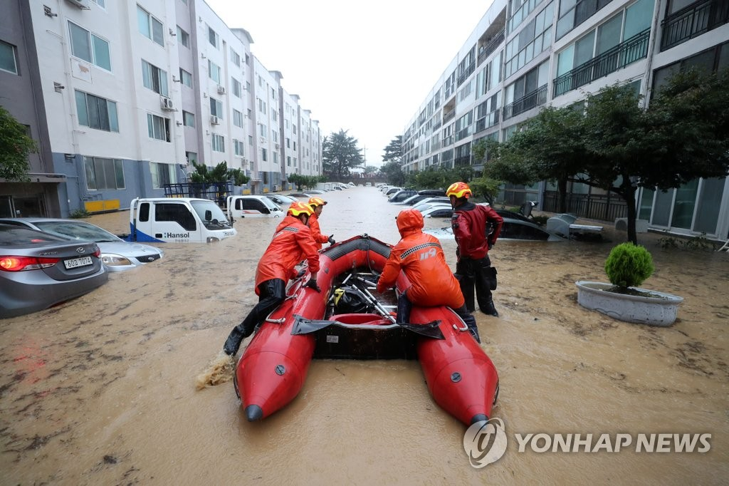Firefighters rescue residents of an apartment in Daejeon, central South Korea, stranded by heavy downpours and subsequent flooding, on July 30, 2020. (Yonhap)