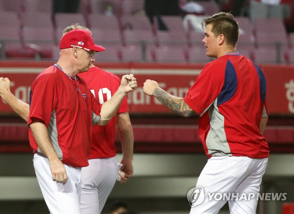 In this file photo from Aug. 6, 2020, Aaron Brooks of the Kia Tigers (R) bumps fists with his manager Matt Williams after their 13-1 victory over the LG Twins in a Korea Baseball Organization regular season game at Gwangju-Kia Champions Field in Gwangju, 330 kilometers south of Seoul. (Yonhap)