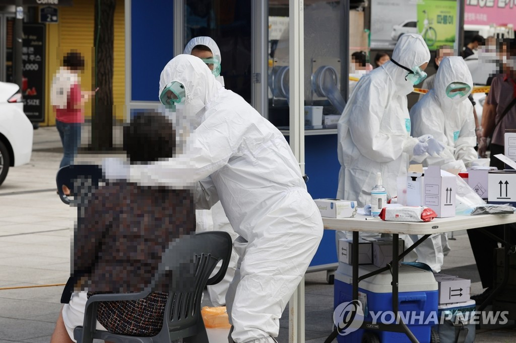 Medical workers carry out new coronavirus tests on visitors at a makeshift clinic located in central Seoul on Aug. 11, 2020. (Yonhap)