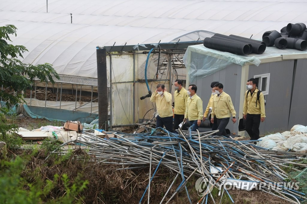 President Moon Jae-in (L) inspects a wrecked farm in Cheonan, South Chungcheong Province, along with other officials on Aug. 12, 2020. (Yonhap)