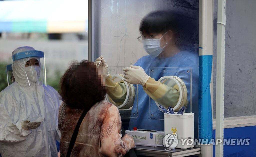 A citizen takes a coronavirus test at a makeshift screening center set up in front of Seoul's Dongdaemun Market on Aug. 14, 2020. (Yonhap)