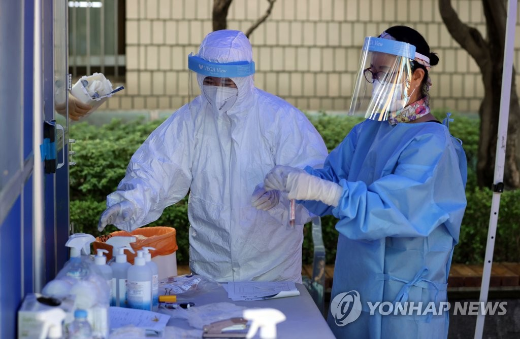 Health workers clad in protective gear prepare to work at a virus screening clinic near a traditional market in Seoul on Aug. 14, 2020. (Yonhap)