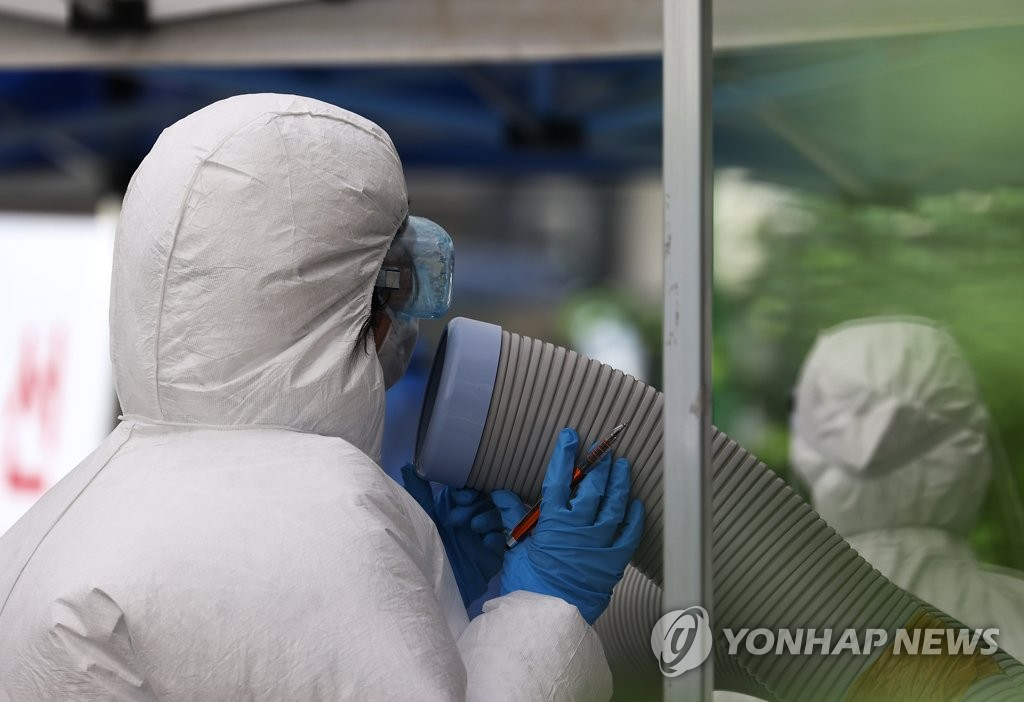 A medical worker stands next to cooling equipment at a makeshift clinic in central Seoul on Aug. 19, 2020. (Yonhap)