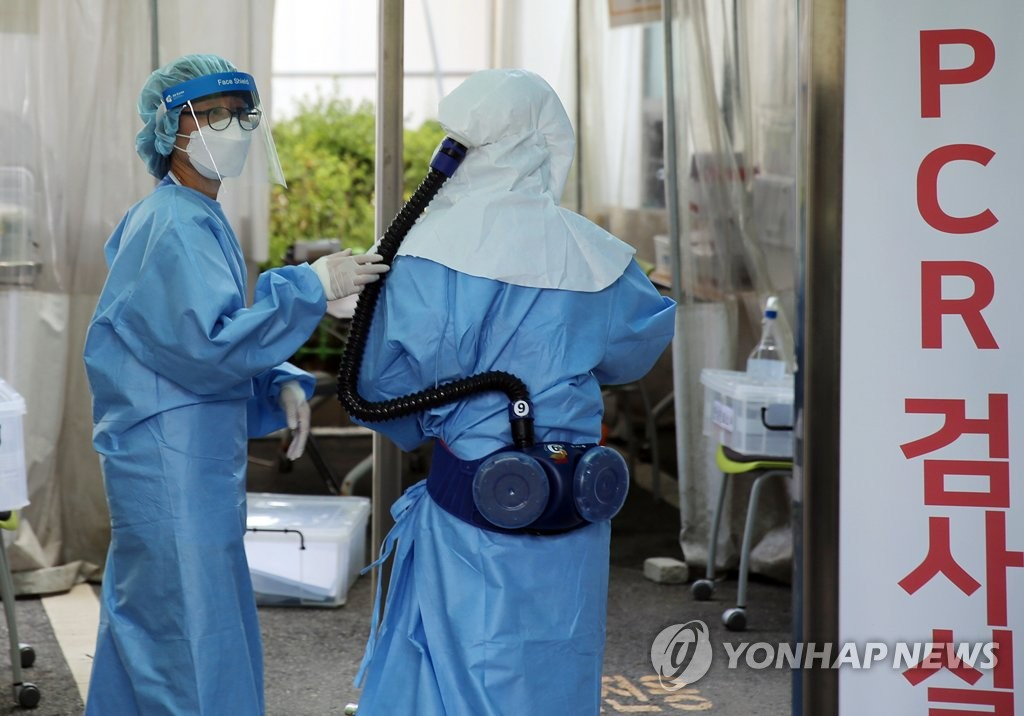 Medical workers wearing protective gear prepare to carry out PCR tests for the new coronavirus at a makeshift clinic of Konyang University Hospital in the central city of Daejeon on Aug. 20, 2020. (Yonhap)