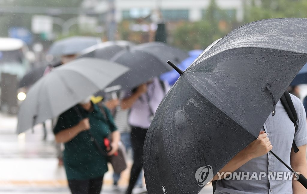 Commuters carry umbrellas in Gwanghwamun in central Seoul on Aug. 27, 2020. (Yonhap)
