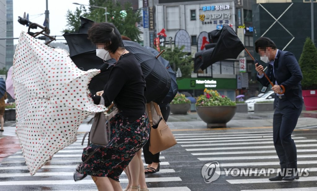 Commuters struggle to hold onto their umbrellas in central Seoul on Sept. 3, 2020. (Yonhap)