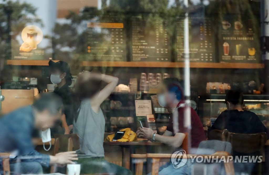Citizens drink coffee at a franchise coffee chain in Seoul on Sept. 14, 2020, as South Korea eased virus curbs in the greater capital region amid slowing coronavirus cases. (Yonhap)