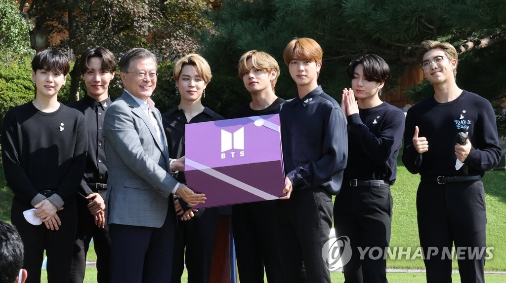 "South Korean President Moon Jae-in (3rd from L) poses holding the ""Year 2039 Gift"" box with K-pop group BTS at the inaugural Youth Day ceremony at Nokjiwon, a verdant garden inside the presidential compound Cheong Wa Dae, in Seoul on Sept. 19, 2020. (Yonhap)"