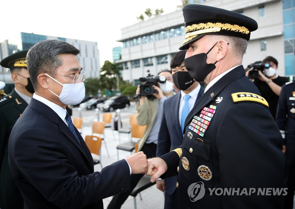 Defense Minister Suh Wook (L) bumps fists with U.S. Forces Korea Commander Gen. Robert Abrams at the inauguration ceremony of new Joint Chiefs of Staff (JCS) Chairman Won In-choul at the JCS headquarters in Seoul on Sept. 23, 2020. (Yonhap)