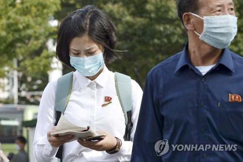 마스크를 쓴 채 걸어가는 평양시민들