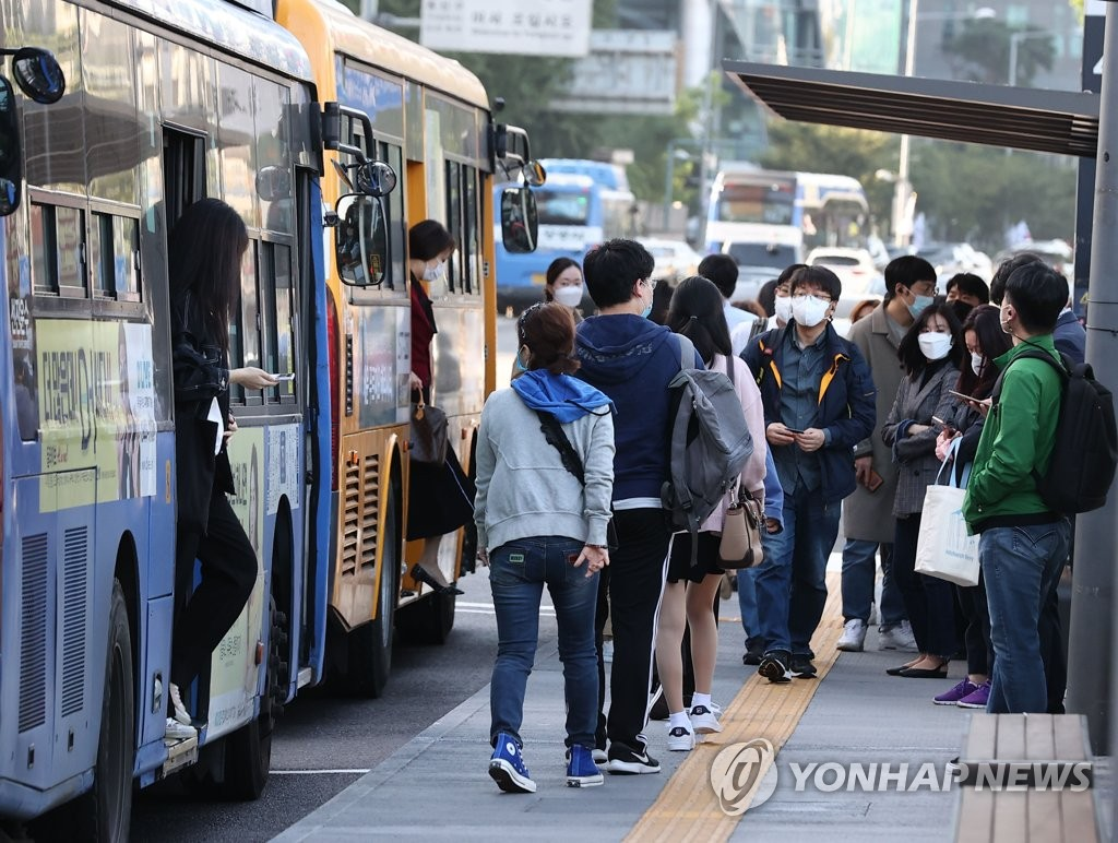 Commuters wearing protective masks wait for buses in central Seoul on Oct. 5, 2020. (Yonhap)