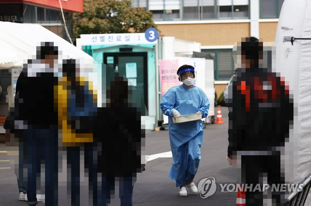 A health worker clad in protective gear prepares to work at a COVID-19 screening clinic on Oct. 7, 2020. (Yonhap)