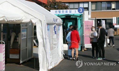 Visitors wait to receive new coronavirus tests at a makeshift clinic located in central Seoul on Oct. 20, 2020. (Yonhap)