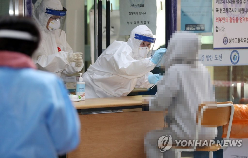 Students receive coronavirus tests at a makeshift clinic in a high school in eastern Seoul on Oct. 27, 2020. (Yonhap)