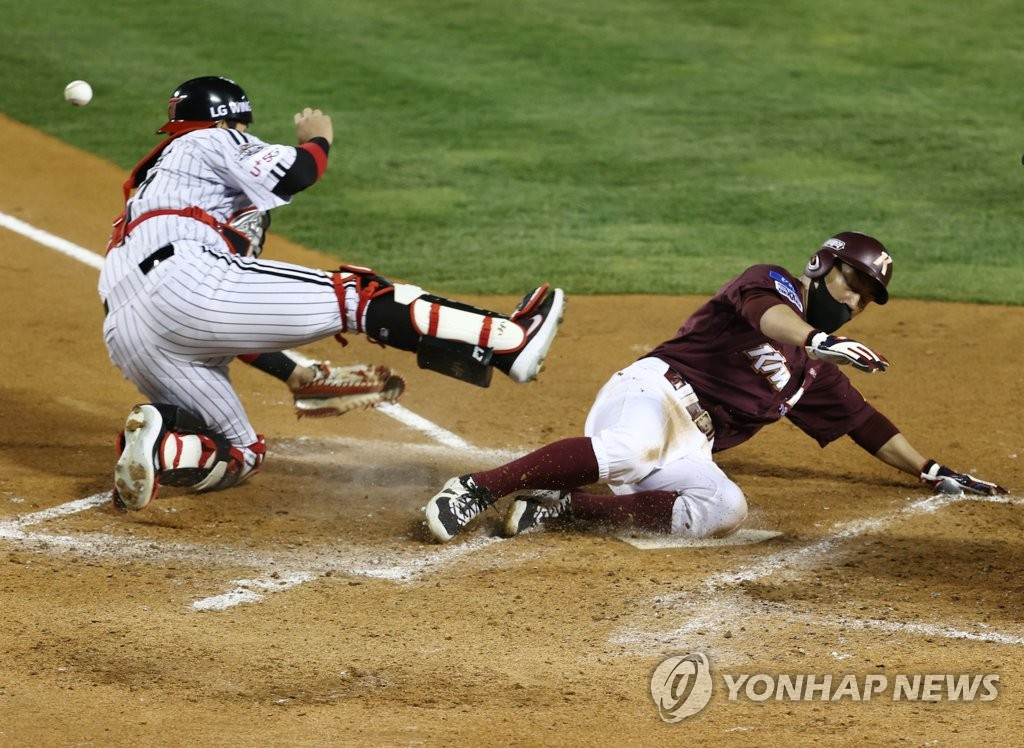 Seo Geon-chang of the Kiwoom Heroes (R) scores past LG Twins catcher Yoo Kang-nam during the top of the fourth inning of a Korea Baseball Organization Wild Card game at Jamsil Baseball Stadium in Seoul on Nov. 2, 2020. (Yonhap)