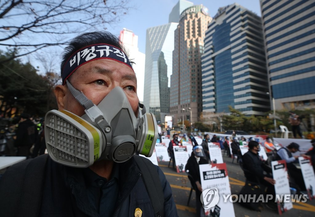 A man wearing a gas mask participates in a rally organized by the Korean Confederation of Trade Unions in Yeouido, southern Seoul, on Nov. 14, 2020. (Yonhap)
