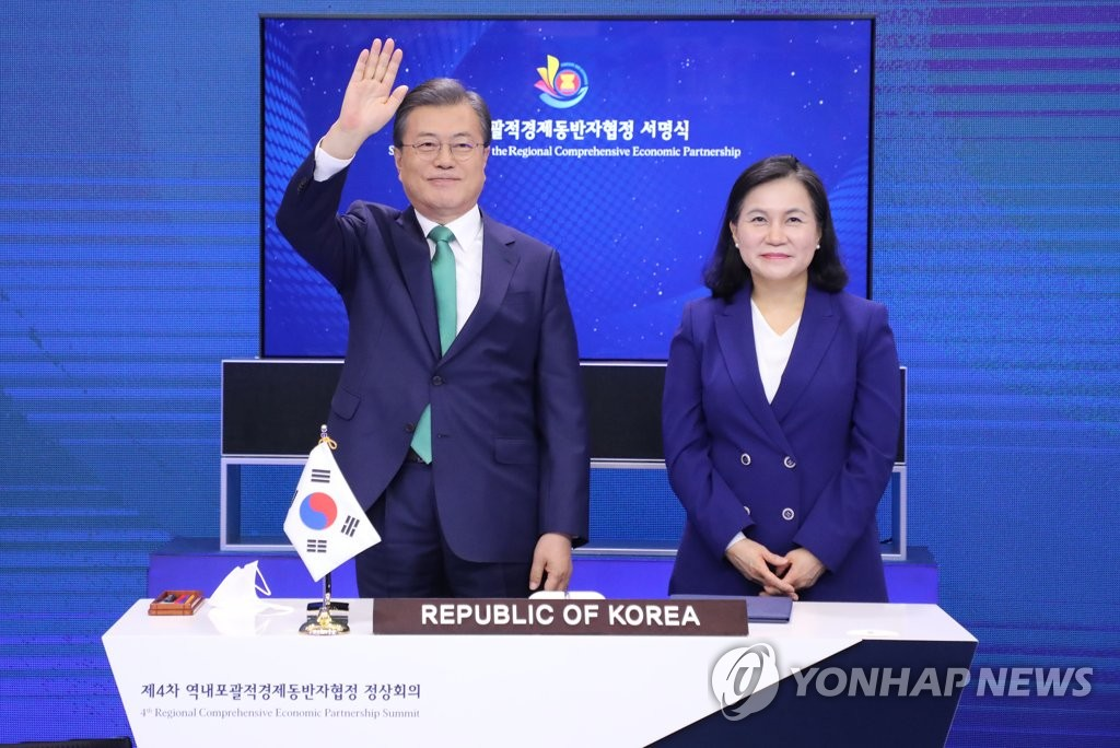 South Korean President Moon Jae-in (L) waves to leaders of other nations, with Trade Minister Yoo Myung-hee standing next to him, during the signing ceremony of the Regional Comprehensive Economic Partnership (RCEP) agreement at Cheong Wa Dae in Seoul on Nov. 15, 2020. (Yonhap)