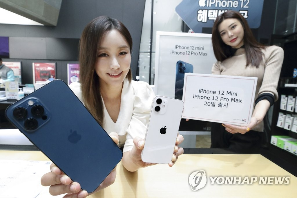 Models showcase Apple Inc.'s iPhone 12 Pro Max (L) and the iPhone 12 mini (R) at a KT Corp. store in this photo provided by the carrier. (PHOTO NOT FOR SALE) (Yonhap)