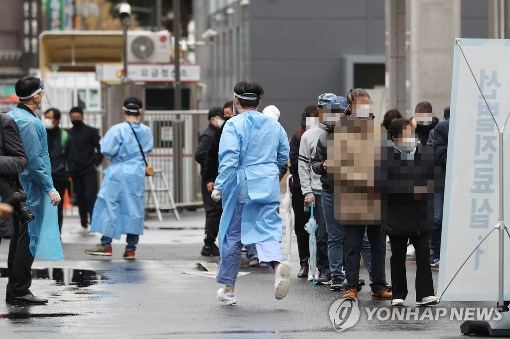 Health workers clad in protective gear prepare to work at a makeshift virus testing clinic in Seoul on Nov. 22, 2020.