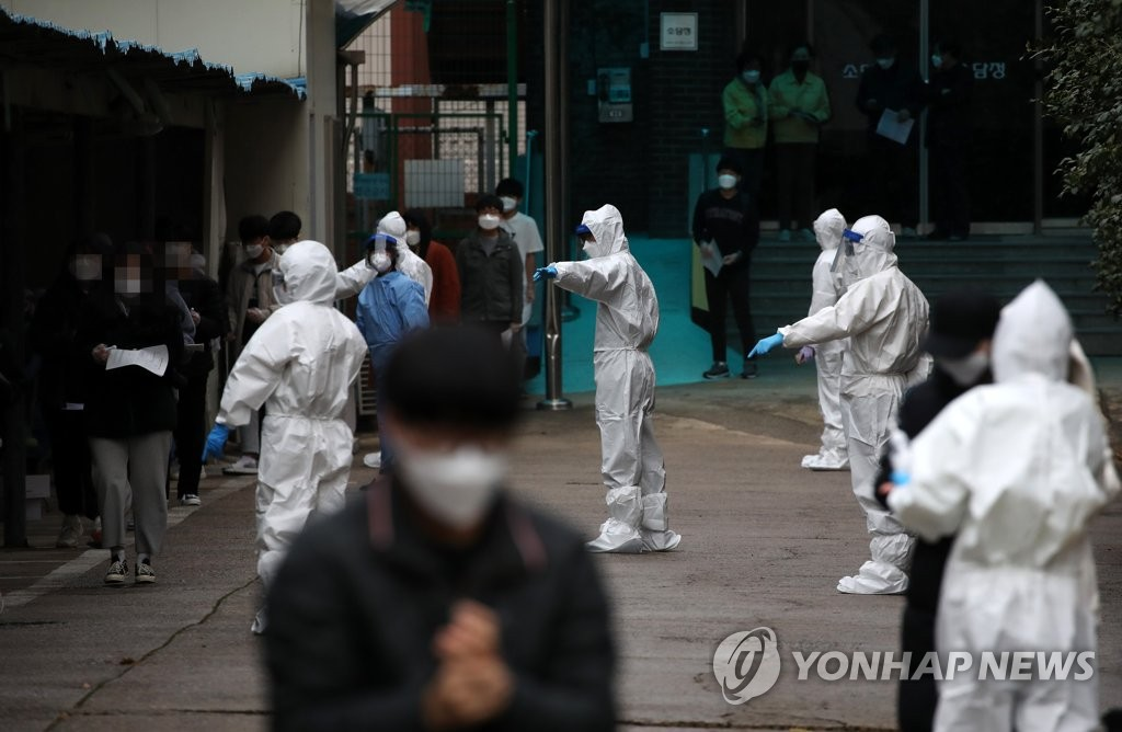 Health workers clad in protective gear guide students as they prepare to receive virus testing at a high school in Gwangju on Nov. 22, 2020, after one student tested positive for the novel coronavirus. (Yonhap)