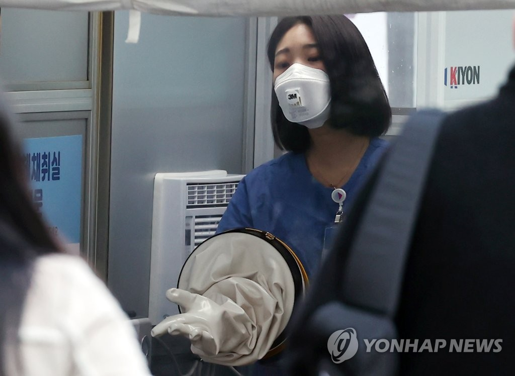A medical worker gets ready for COVID-19 testing at the National Medical Center on Nov. 23, 2020. (Yonhap)