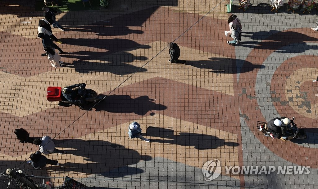 Pedestrians are shown in this photo taken in front of Hongik University in western Seoul on Nov. 23, 2020. (Yonhap)