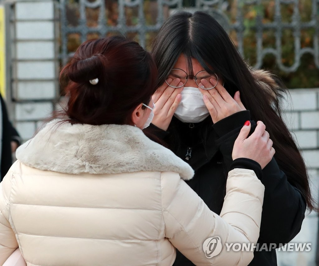 A student taking the College Scholastic Ability Test cries as she parts with her mother outside a high school in Busan, 453 kilometers southeast of Seoul, on Dec. 3, 2020. (Yonhap)