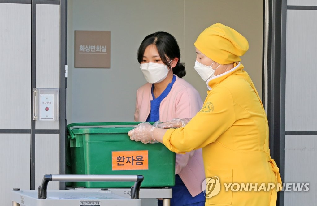 Health care workers deliver packed lunches to coronavirus-infected students taking the College Scholastic Ability Test at a medical facility in Pohang, 374 kilometers southeast of Seoul, on Dec. 3, 2020. (Yonhap)