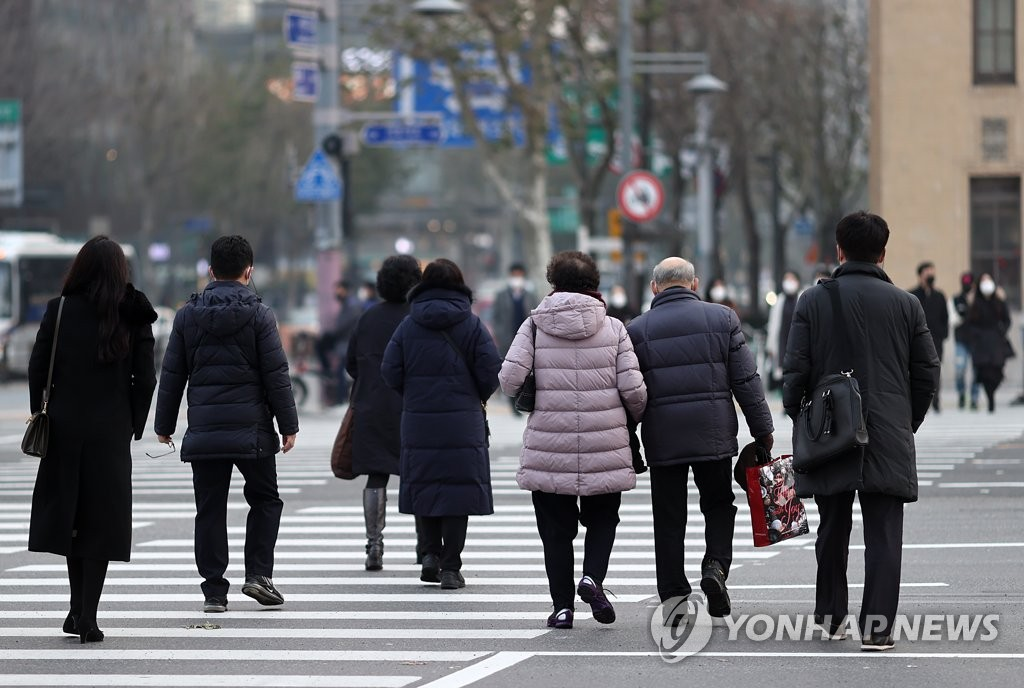 Citizens cross a street in downtown Seoul on Dec. 7, 2020, as the new virus cases stayed above 600 for the second consecutive day. (Yonhap)