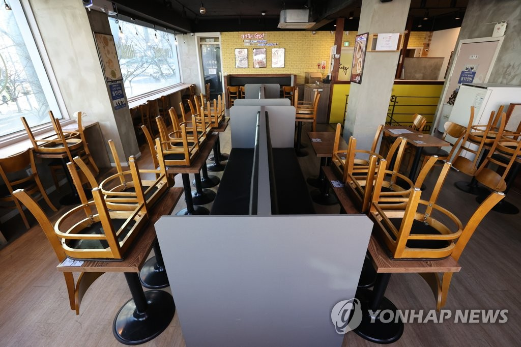 Chairs are turned upside down on tables at a coffee shop in southern Seoul on Jan. 6, 2021, due to COVID-19 restrictions banning dining in at cafes. (Yonhap)
