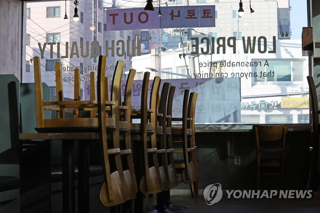 Chairs are turned upside down on tables inside a coffee shop in southern Seoul on Jan. 6, 2021, amid the government's COVID-19 restrictions on dining in at cafes. (Yonhap)
