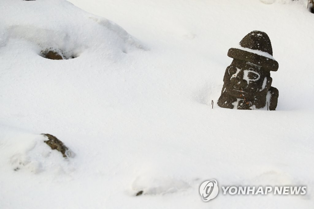 "A ""dolhareubang"" statue is half buried in the snow in Jeju on Jan. 7, 2021. (Yonhap)"