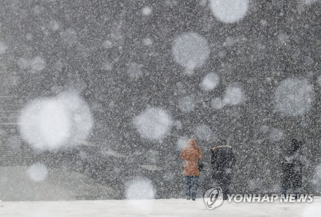 People walk under falling snow on Ewha Womans University's campus in Seoul on Jan. 12, 2021. (Yonhap)