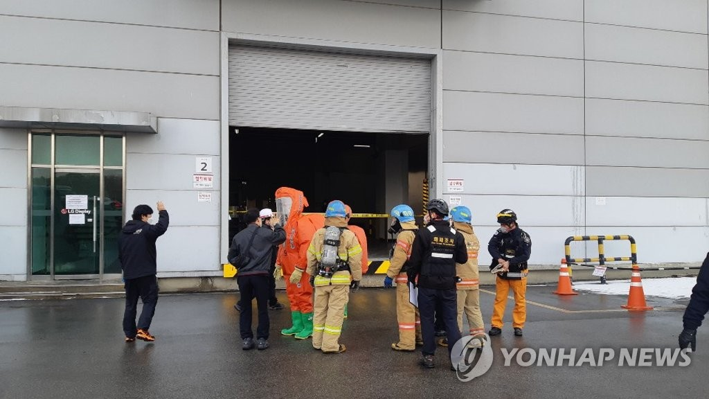 This photo provided by Paju Fire Station shows rescue officials working at LG Display Co.'s plant in Paju, north of Seoul, to handle a toxic chemical leak at the factory. (PHOTO NOT FOR SALE) (Yonhap)