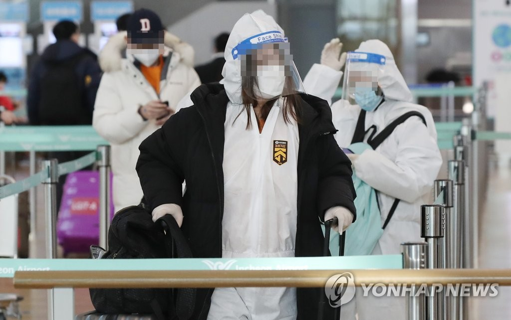 Passengers clad in protective gear wait at a check-in counter at Incheon International Airport, west of Seoul, on Jan. 14, 2021 (Yonhap)