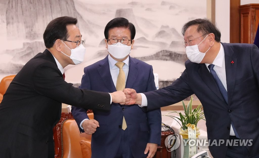 National Assembly Speaker Park Byeong-seug (C) watches the floor leaders of the ruling Democratic Party and the main opposition People Power Party -- Kim Tae-nyeon and Joo Ho-young -- bumping fists during their meeting at his office in Seoul on Feb. 1, 2021. (Yonhap)