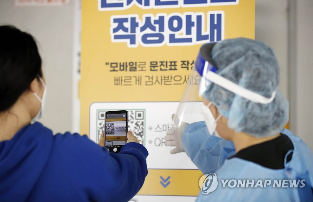 A medical worker assists a visitor with a QR code-based registration system at a medical clinic in Gwangju, 329 kilometers south of Seoul, on Feb. 22, 2021, in this photo provided by the Buk Ward of the city. (PHOTO NOT FOR SALE) (Yonhap)