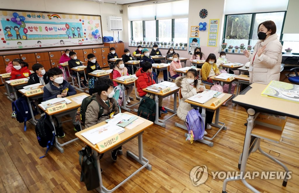 This March 2, 2021, photo shows children and a teacher having an in-person class while wearing face masks at an elementary school in Incheon, about 40 kilometers west of Seoul. (Yonhap)