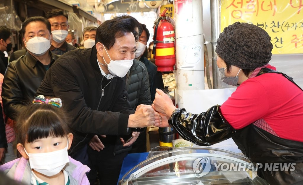 This file photo shows Oh Se-hoon, former candidate of the main opposition People Power Party for the April 7 Seoul mayoral by-election, bumping fists with a merchant during a visit to a traditional market in Seoul on March 9, 2021. (Yonhap)
