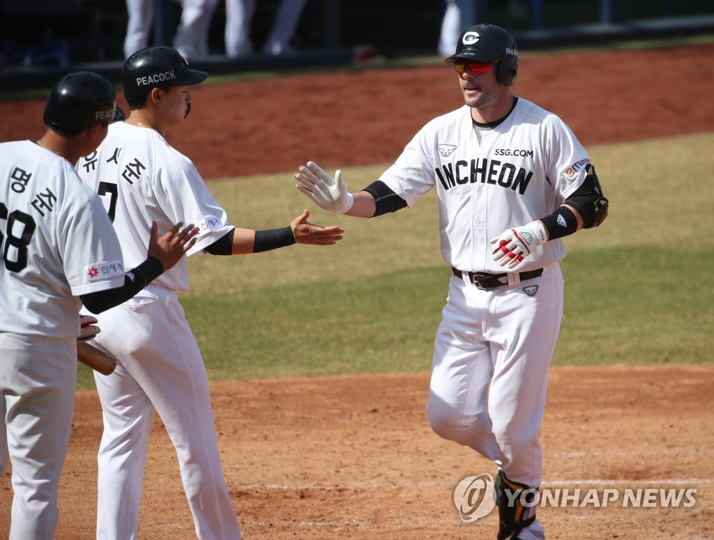 Jamie Romak of the SSG Landers (R) is greeted at home plate by teammate Yoo Seo-jun (C) and Ko Myoung-jun after hitting a three-run home run against the Samsung Lions in the top of the sixth inning of a Korea Baseball Organization spring training game at Daegu Samsung Lions Park in Daegu, 300 kilometers southeast of Seoul, on March 16, 2021. (Yonhap)