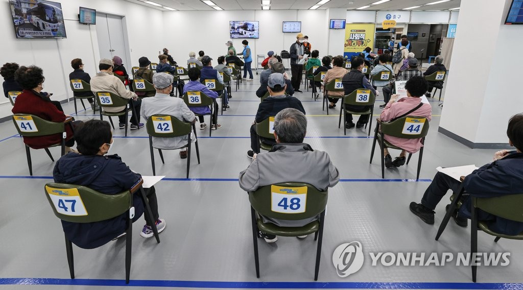 Senior citizens wait to receive COVID-19 jabs at a district office in eastern Seoul on April 9, 2021. (Yonhap)
